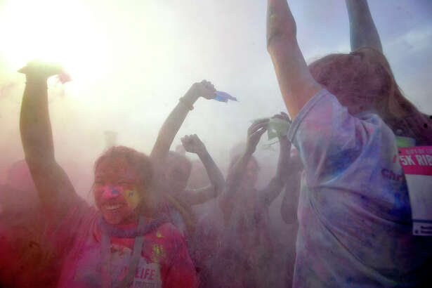 Participants celebrate as they take part in the final color blast during the Gift of Life's 6th annual Julie Richardson Procter 5K Ribbon Run Color Rush Saturday in downtown Beaumont. Photo taken Saturday, October 1, 2016 Kim Brent/The Enterprise