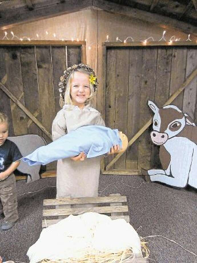 A child dresses as Mary in front of a life-size stable in the Photo Room at the Nativity Exhibit. Photo: Submitted Photo / @WireImgId=2652940