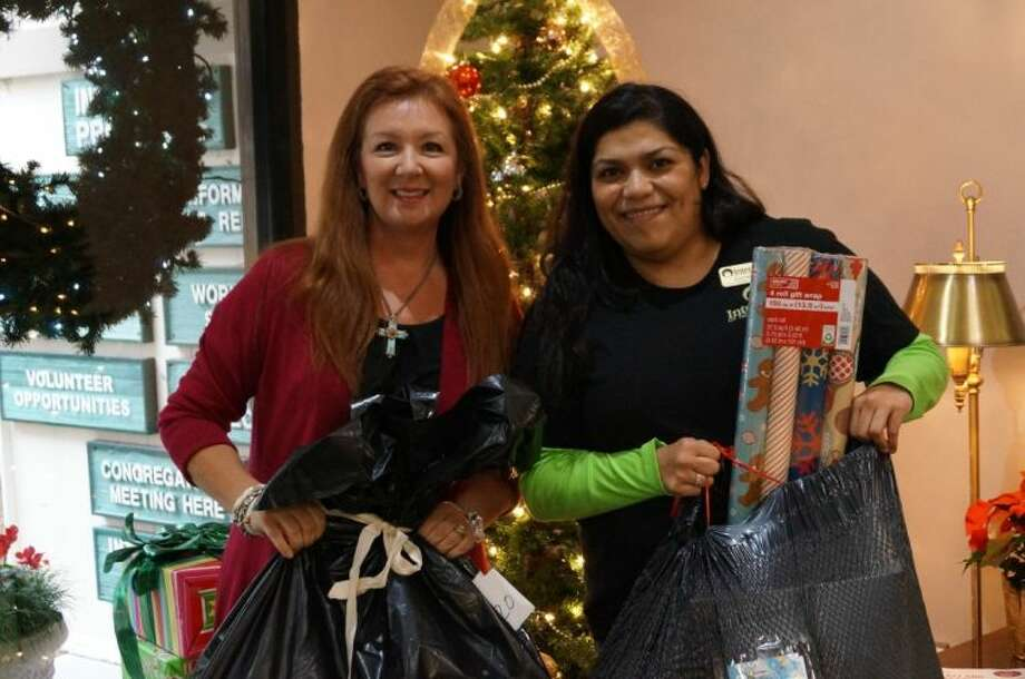 Teresa Yniguez, left, is pictured with Lucy Gomez, Family Services manager at Interfaith of The Woodlands, delivering a donation as part of Interfaith's holiday Giving program.