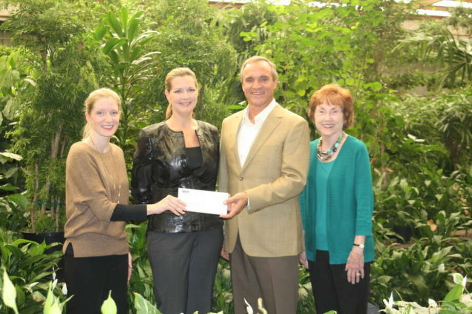 Rachel Leaman (left) and Charlene Pate (right), fundraising committee co-chairs for the Fort Bend Children's Discovery Center, accept a $50,000 donation from Diana and Brad Wander (center) to sponsor the Town Square Park within the museum's Kidtropolis exhibit. Photo: Submitted Photo