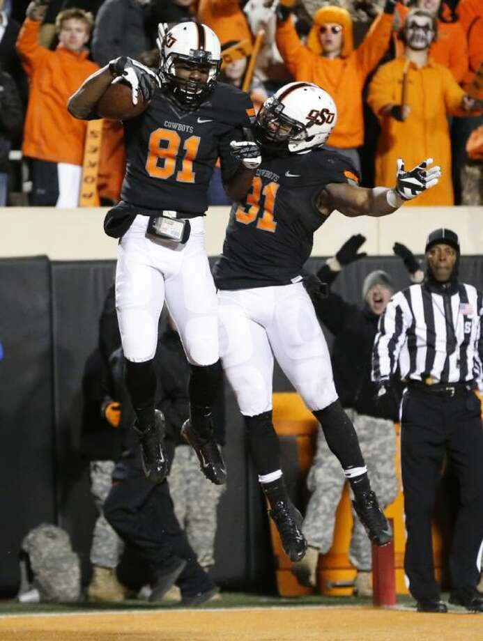 Oklahoma State's Jhajuan Seales (81) and Jeremy Smith celebrate a touchdown against Baylor on Nov. 23 in Stillwater, Okla. The Cowboys won, 49-17.