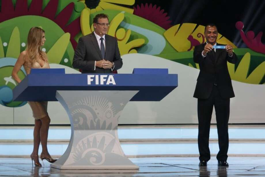 Former soccer great and World Cup winner Cafu from Brazil holds the ticket of Brazil as Brazilian actress Fernanda Lima, left, and FIFA Secretary General Jerome Valcke look on during the draw ceremony for the 2014 World Cup.