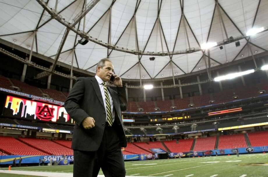 Missouri coach Gary Pinkel talks on a cellphone Friday as he waits for the Tigers' players to arrive at the Georgia Dome ahead of Saturday's Southeastern Conference championship game against Auburn in Atlanta.