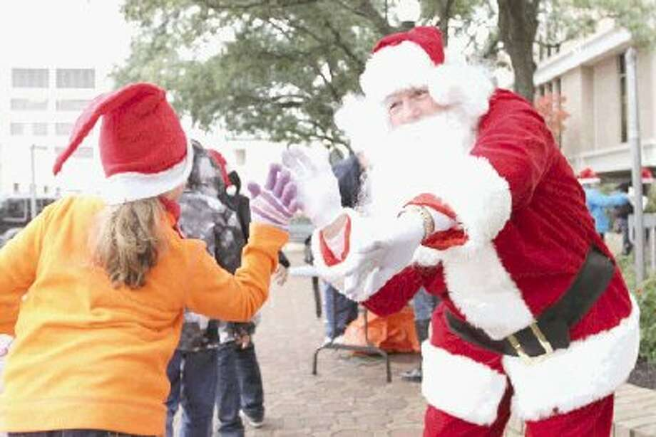 Santa Claus gives New Caney ISD students high-fives in front of the Montgomery County Courthouse Friday. Volunteers accepted donated food items at various locations throughout Montgomery County to benefit the Montgomery County Food Bank. Photo: Staff Photo By Jason Fochtman / Conroe Courier