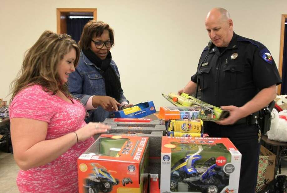Samantha Cosme, Judy Eaton and Deputy Neil Adams sort through some of toys donated to Toyz For Kidz on Friday, Dec. 6. The toys will be given to underprivileged children in San Jacinto County in time for Christmas. Photo: VANESA BRASHIER