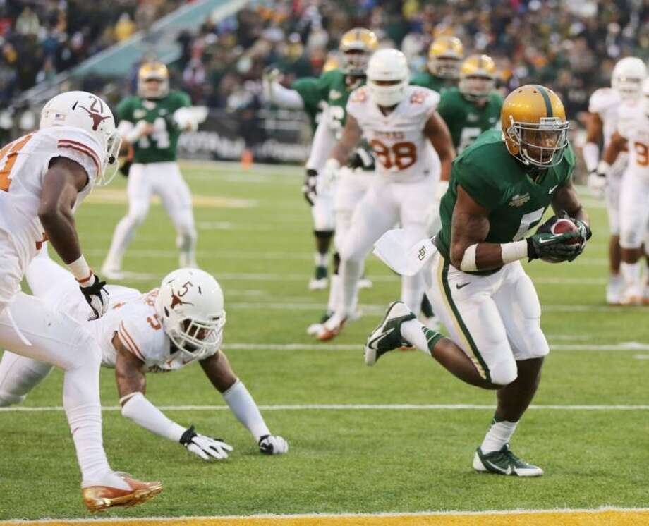 Baylor's Antwan Goodley (5), right scores past Texas safety Josh Turner (5) and cornerback Duke Thomas (21). Baylor won 30-10 to take the Big 12 title.