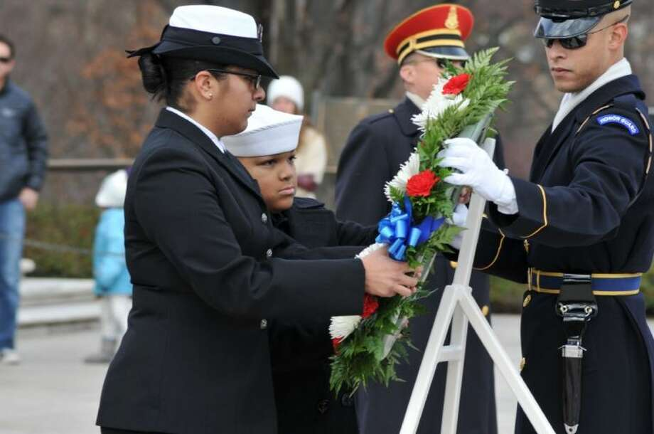 A member of the U.S. Army 3rd Infantry Honor Guard hands Information Systems Technician Seaman Yesenia Munoz, 19, a Sailor from Naval History and Heritage Command (NHHC) and a native of Houston, Texas, and Naval Sea Cadet Saddique Stevens the wreath they are to lay at Arlington National Cemetery's Tomb of the Unknowns, as Yeoman Seaman Victoria Ruiz, from NHHC a Hacienda Hieghts, Calif. Resident, and Naval Sea Cadet Nicklaus Tollmeo prepare for the start of the wreath laying ceremony . The wreath, honoring veterans of the Dec. 7, 1941 attack on Pearl Harbor, was sponsored by the Naval Order of the United States and is part of a world-wide observance honoring the service and sacrifice of those who were there on that day of infamy. Photo: U.S. Navy Photo By Mass Communic