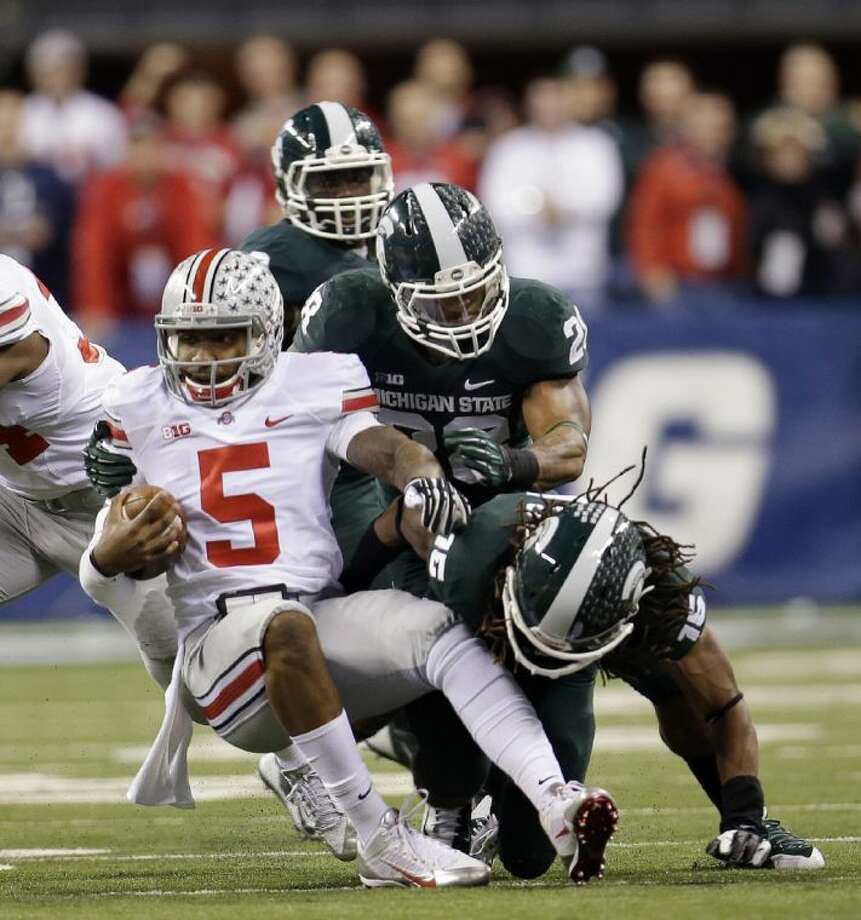 Michigan State's Trae Waynes (15) and Denicos Allen tackle Ohio State quarterback Braxton Miller in the Big Ten championship game. The Spartans led the second-ranked Buckeyes 34-24 late in the fourth quarter at press time.