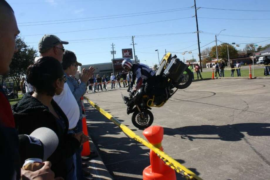 "Guests surveyed a variety of bikes: vintage, classic, modern and collectable and watched as champion stunt rider Chris ""Teach"" McNeil took a few spins and demonstrated some riding techniques in the school parking lot. Photo: Y.C. OROZCO"