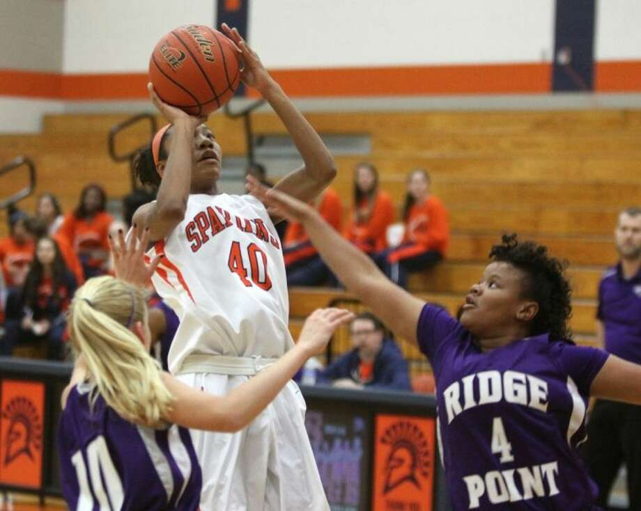 Seven Lakes' Cydney Varner shoots against Ridge Point's Ashlin Riggs during the 2013 Nike Classic. The Lady Spartans clinched their fourth straight district title Feb. 3. Photo: Alan Warren