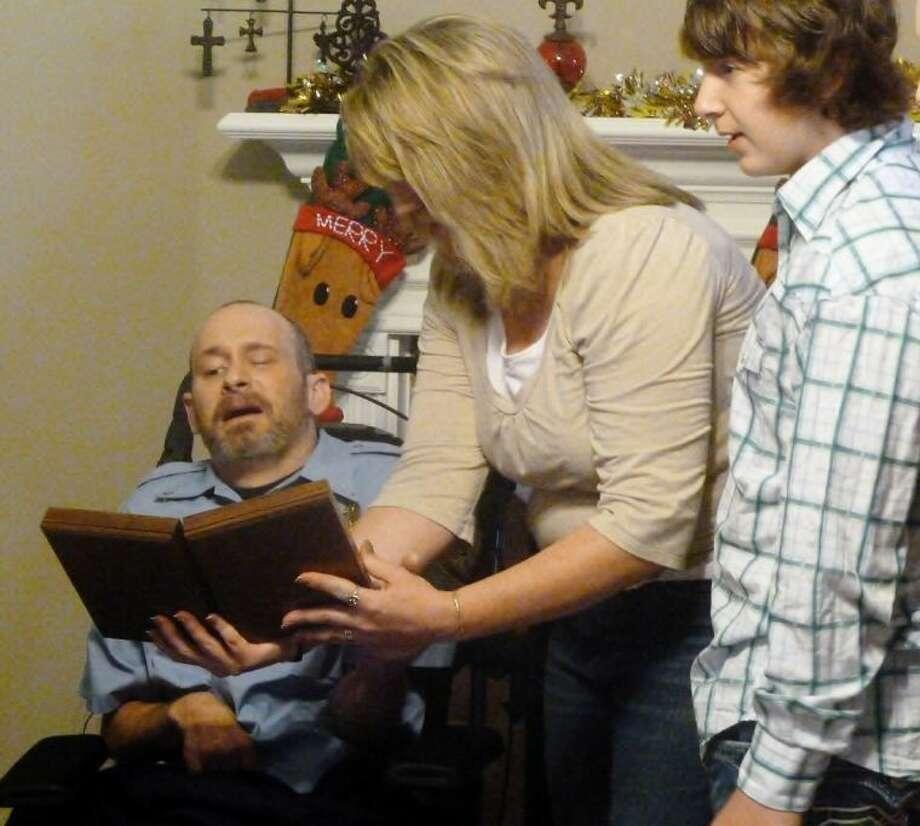 Jacki Dowling shows her husband Bill Dowling the Liberty Mutual Firemark Award.