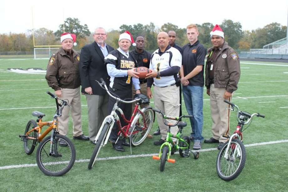 Preparing for the annual Battle of the Bend are, from left, Major Chad Norvell, Fort Bend County Sheriff's Office; Jack Molho, Toys for Tots - Fort Bend County; Fort Bend County Sheriff Troy E. Nehls; Sgt. Antione Parker, 1st Battalion, 23rd Marines and Toys for Tots; Sugar Land Police Chief Doug Brinkley; Derrick McCullar, Sugar Land Police Department; Sgt. Daniel Hennelly, 1st Battalion, 23rd Marines and chairman of the Toys for Toys in the Greater Houston Area; and Deputy Frank Davis, Fort Bend County Sheriff's Office and founder of the annual Fort Bend Holiday Bowl. Photo: Courtesy FBCSO