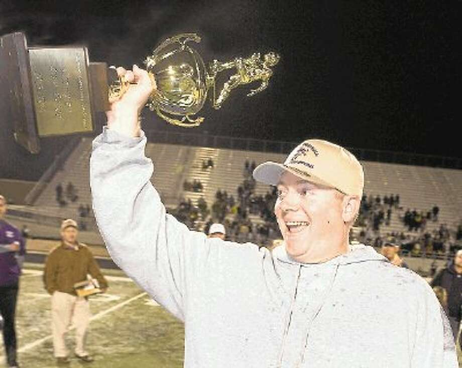 Kinkaid head football coach Nathan Larned holds up the Southwest Preparatory Conference championship trophy minutes after the Falcons defeated Dallas St. Mark's in mid-November to win the SPC for the third time in five years. The Falcons were 11-0 this season and 6-0 after Larned took over the job from Stephen Hill midway through the season. They were also the SPC South Zone champions with a 6-0 record. Photo: Kevin B Long / ©2013 Kevin B Long. All rights reserved.
