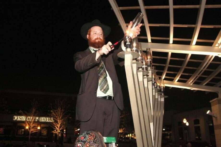 Rabbi Dovid Goldstein lights the menorah last week during the Menorah Lighting at La Centerra's Central Green in Katy. Photo: Alan Warren