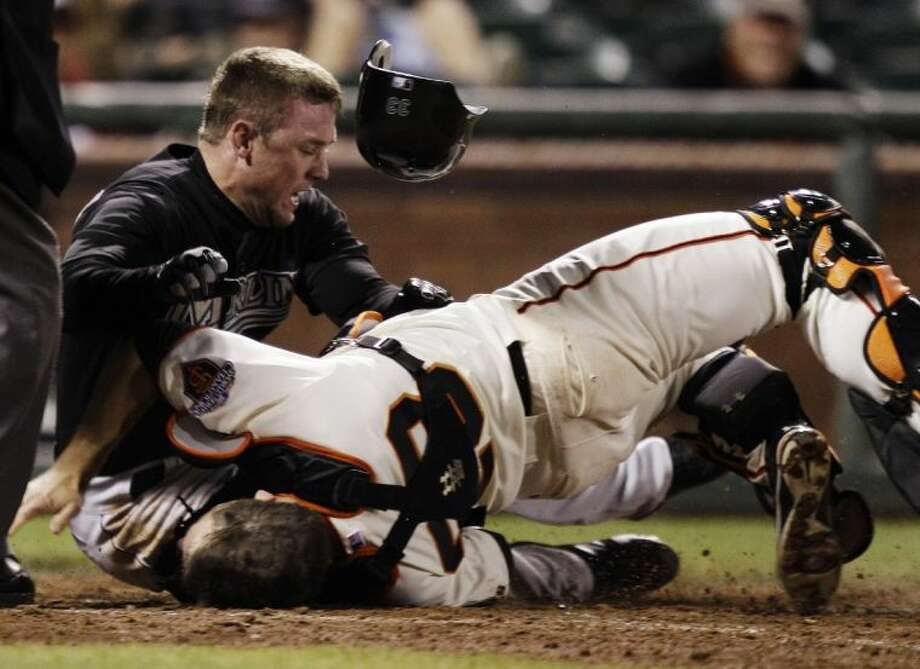 The Florida Marlins' Scott Cousins, left, collides with San Francisco Giants catcher Buster Posey at home plate on May 25, 2011. Posey broke the fibula and tore three ankle ligaments in his left leg on the play, which ended his season.