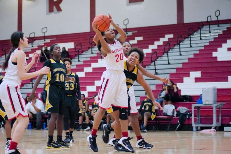 Clear Brook's Twon Mackey (20) fights to get a shot past Fort Bend Marshall's Asia Jones (42) during the Peggy Whitley Classic basketball tournament Friday. Photo: KIRK SIDES