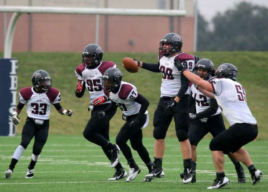 Pearland defensive lineman Kevin Harvey (99) celebrates with teammates Jason King (33), Avery Jordan (95), Jonathan Goff (27), Alfred Sosa (42) and Ronnie Fraser (55) after Harvey's fourth-quarter interception that helped preserve a 10-3 win over Cy Fair. Pearland takes on San Antonio Madison at 3 p.m., next Saturday in Waco in the state semifinals. Photo: KAR HLAVA