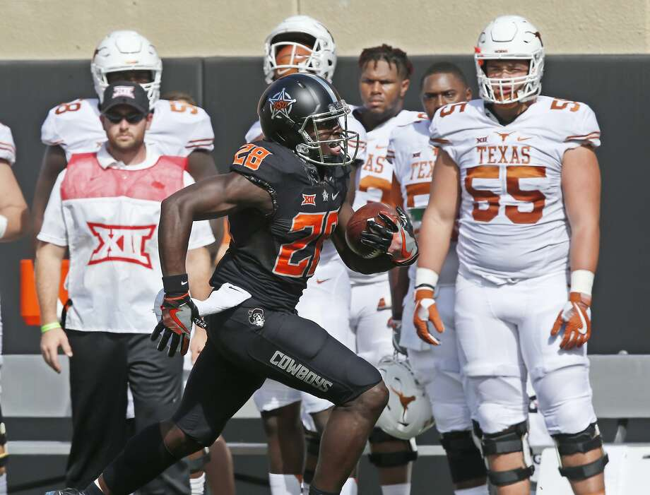 Oklahoma State wide receiver James Washington (28) runs past the Texas bench and into the end zone for a touchdown in the first quarter of an NCAA college football game in Stillwater, Okla., Saturday, Oct. 1, 2016. (AP Photo/Sue Ogrocki) Photo: Sue Ogrocki, Associated Press