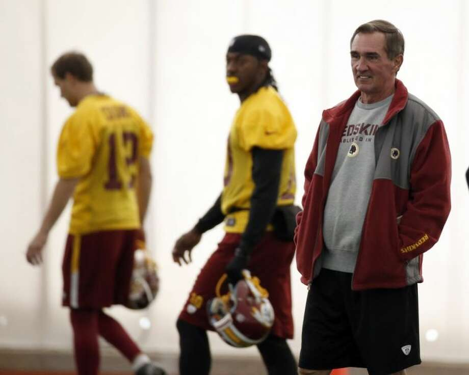 Washington Redskins quarterbacks Kirk Cousins, left, and Robert Griffin III walk behind coach Mike Shanahan during practice Wednesday in Ashburn, Va. Cousins will start for the Redskins on Sunday at Atlanta, and Griffin III will be the No. 3 quarterback behind Rex Grossman.