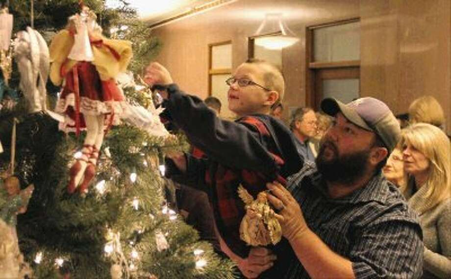 Kenneth Woodard helps Kamden Moran hang an ornament during the annual Montgomery County Tree of Angels dedication ceremony at the Montgomery County Courthouse on Thursday evening. Friends and families of victims of violent crimes came together to remember their loved ones. / Conroe Courier