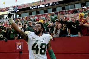 Baylor defensive back Travon Blanchard takes a selfie with a fan's phone as they celebrate their 45-42 victory over Iowa State during an NCAA college football game, Saturday, Oct. 1, 2016, in Ames, Iowa. (AP Photo/Justin Hayworth)
