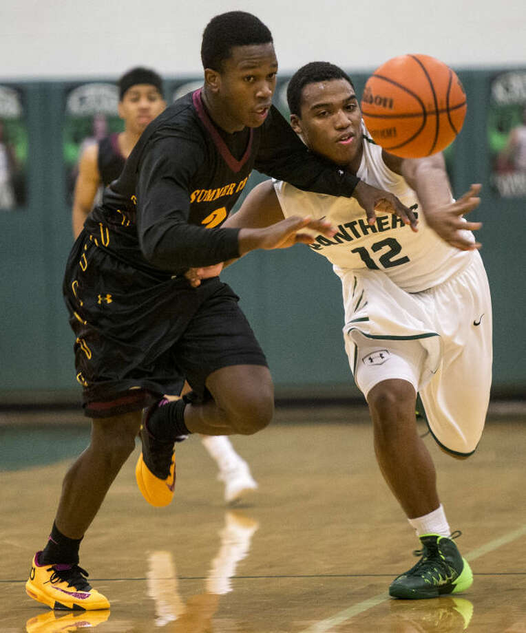 Summer Creek's Treylan Matthews, left, and Kingwood Park's Jordan Powell fight for a loose ball during Summer Creek's victory over Kingwood Park on Dec. 13, 2013, at Kingwood Park High School. (Photo by ANDREW BUCKLEY/The Observer) Photo: ANDREW BUCKLEY
