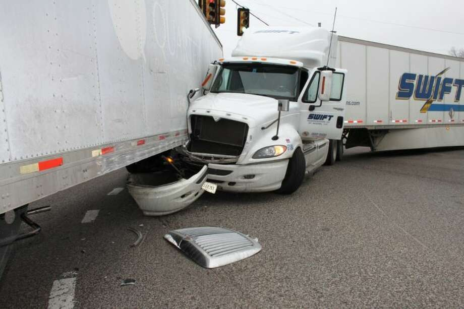 The bumper of an 18-wheeler became lodged under the trailer of another 18-wheeler at the intersection of Houston and Washington streets in Cleveland on Friday, Dec. 13. Both trucks were making southbound turns and collided. Photo: VANESA BRASHIER