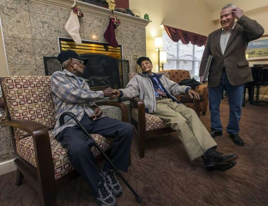 Richard Overton, 107, left, and Elmer Hill, 107, center, shake hands before Austin Mayor Lee Leffingwell presents a proclamation acknowledging and thanking Overton, and Hill for their service on Friday. Overton is Austin's oldest living World War II veteran and Hill is Henderson, Texas' oldest living World War II veteran.
