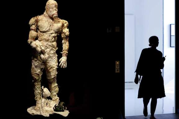 A woman walks past a Golem costume of the Malenki Theater in Tel Aviv as she arrives for a press presentation for the 'Golem' exhibition at the Jewish Museum in Berlin, Germany, Thursday, Sept. 22, 2016. The myth of artificial life, from homunculi and cyborgs to robots and androids, is the focus of an exhibition about the Golem at the Jewish Museum Berlin. The exhibition runs from Sept. 23, 2016 until Jan. 29, 2017. (AP Photo/Michael Sohn)