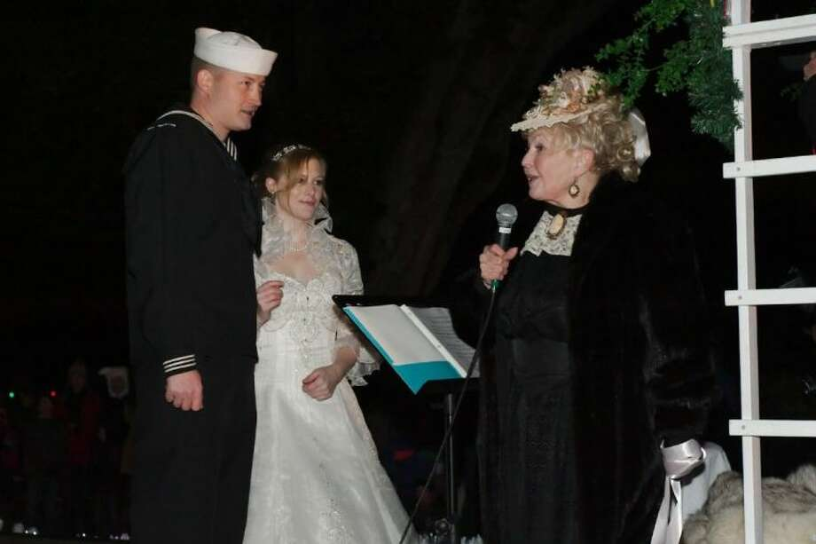 'Victorian Lady' J'Nean Henderson officiates as Navy Petty Officer 1st Class Jake Dillon and Bridget Murray celebrate their marriage during the annual League City Holiday in the Park Grand Night Parade Saturday, Dec. 7. Photo: KIRK SIDES