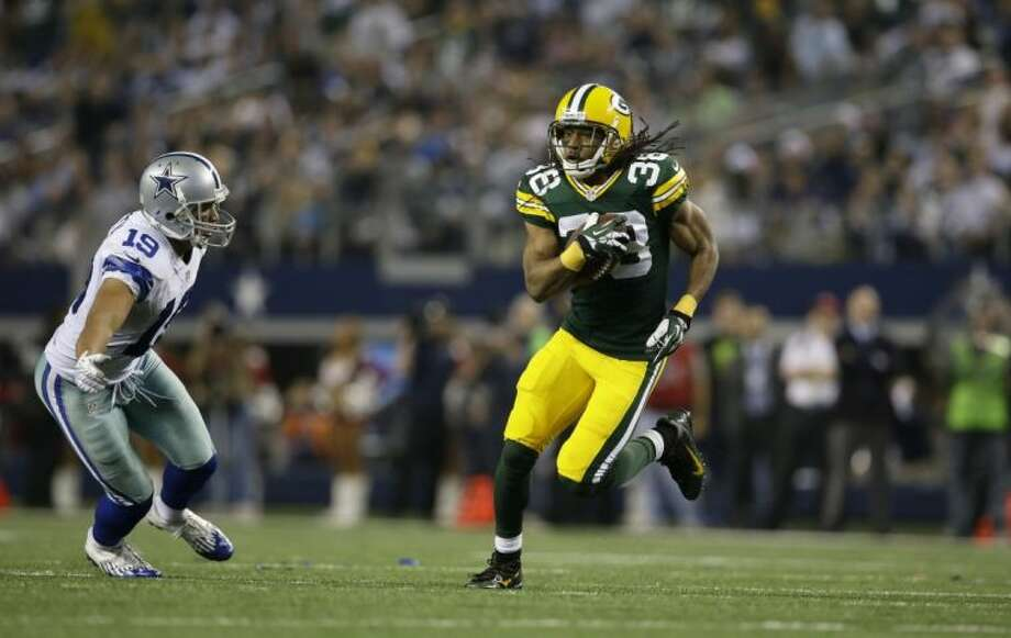 Packers cornerback Tramon Williams, right, returns an interception against the Dallas Cowboys in the second half. At left is the Cowboys' Miles Austin.