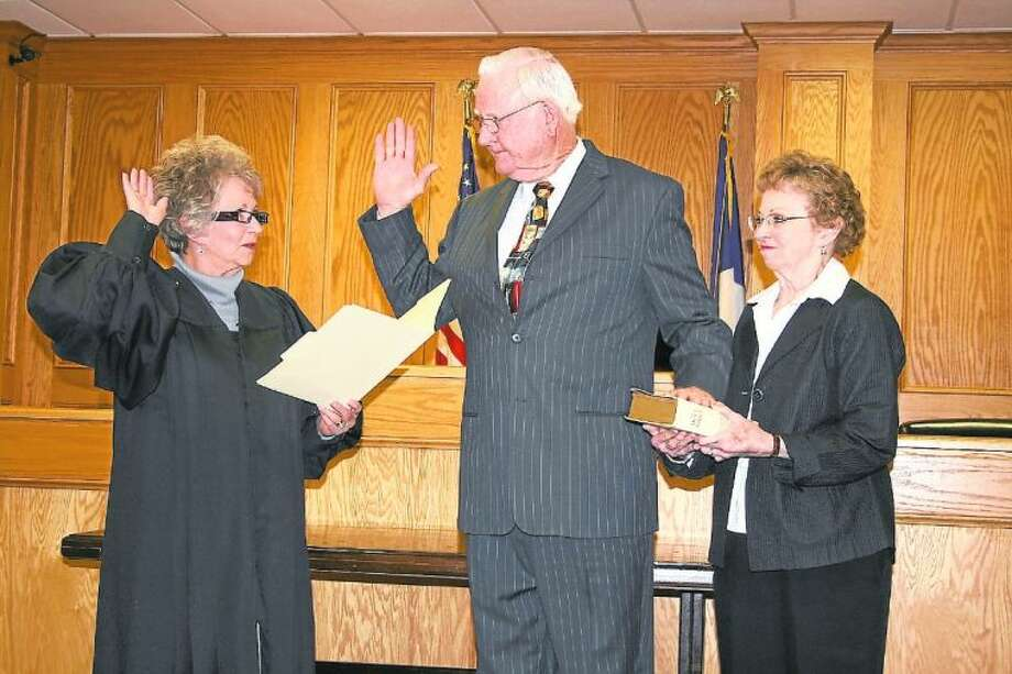 With his hand on a Bible held by his wife, Carolyn, Cleveland Municipal Court Judge Bob Steely takes his oath of office on Thursday, Feb. 14. He was sworn in by his friend and fellow judge, Pct. 6 Justice of the Peace Peggy Dunn (left). Photo: VANESA BRASHIER