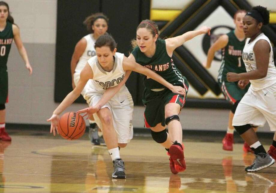The Woodlands guard Paulina Bremer tips the ball away from Conroe guard Lindsey George during a District 14-5A game on Tuesday at Conroe High School. To view or purchase this photo and others like it, visit HCNpics.com.