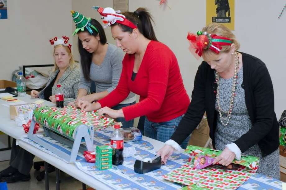 Johnstone Supply volunteers Larissa Mejia, Starla Tessitore and Kiki Carroll wrap packages during the Operation Homefront Holiday Toy Drive Event providing toys for children of military personnel at Ellington Airport Thursday, Dec. 12. Photo: KIRK SIDES