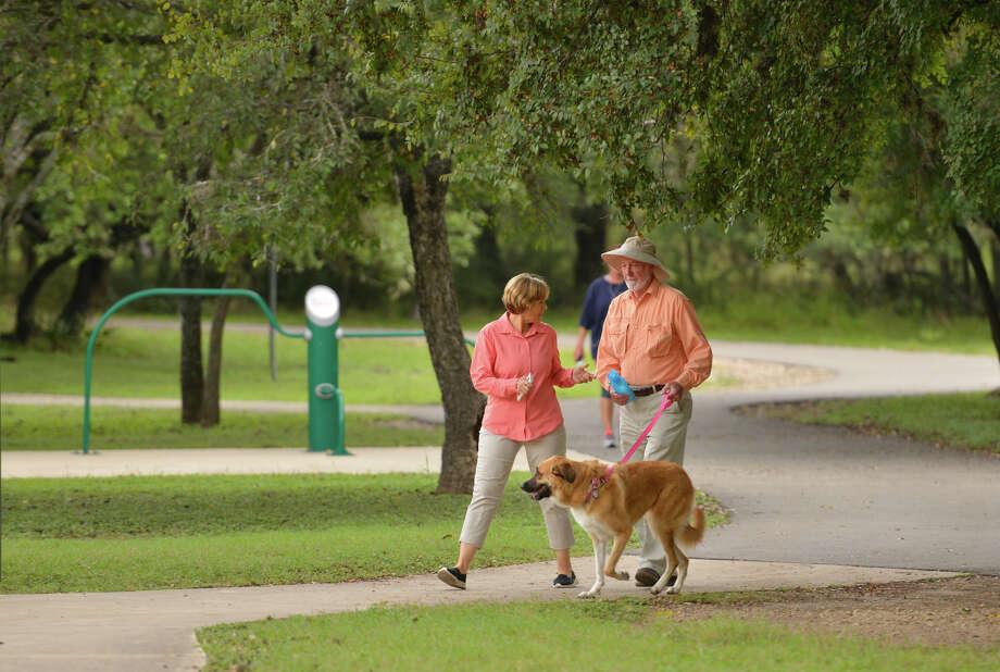 A couple walk their dog in McAllister Park which is set to undergo major changes under a 2017 bond proposal. Photo: Robin Jerstad / San Antonio Express-News