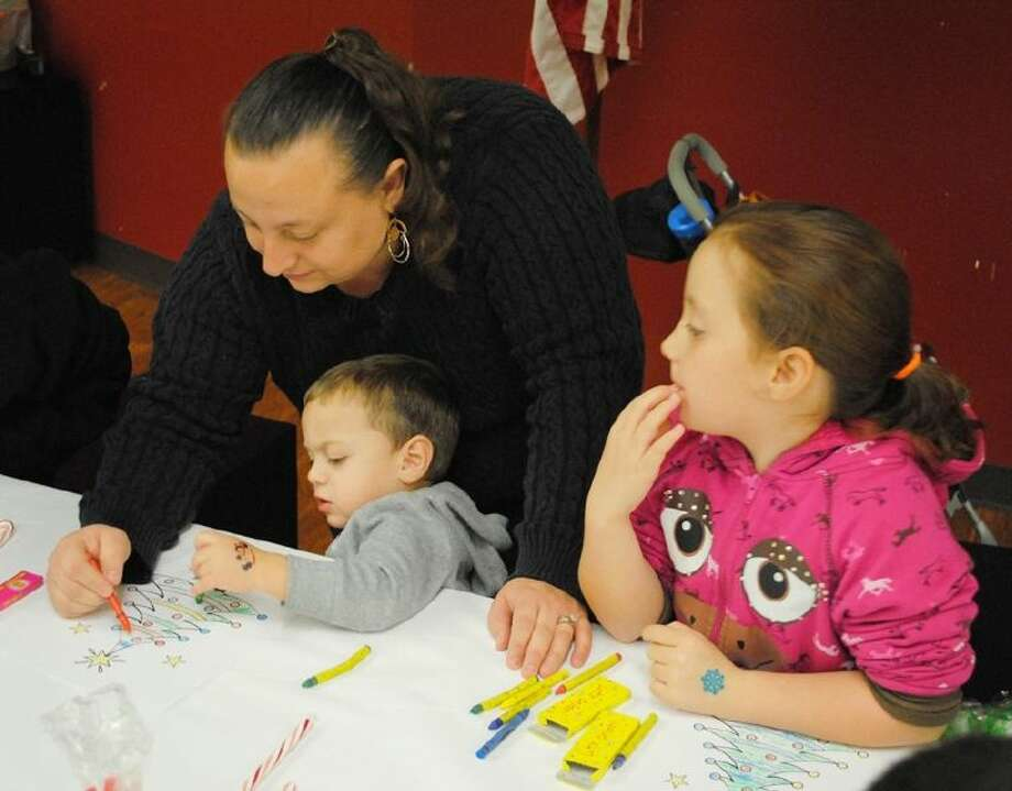 Glendy Paz, of Alvin, center, colors a Christmas tree with Diego Paz, 2 and his sister Jennifer Paz, 10 during the Breakfast with Santa event on December 7. Photo: Courtesy ACC