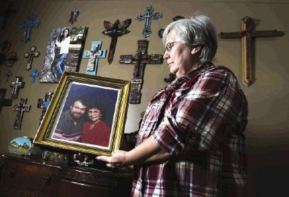 Conroe resident Donna Kinser poses with an image of she and her husband, Gregory, who died Sunday while recovering from heart surgery at Conroe Regional Medical Center. Kinser is left wondering if her husband death might be one of the four deaths related to a mysterious illness reported at Conroe Regional Medical Center this week. / Conroe Courier