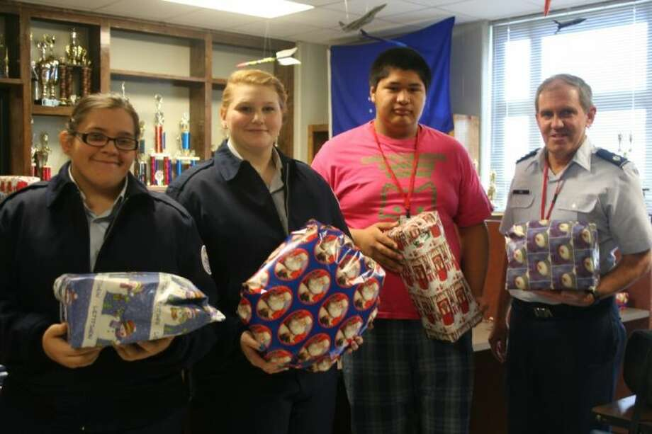 Cadets in the Cleveland High School Air Force Junior ROTC program, including Alissa Barella, Carlie Ott and Angel Martinez, along with Lt. Col. Robert Hunt, helped raise funds to buy presents for more than 250 local children. Photo: STEPHANIE BUCKNER