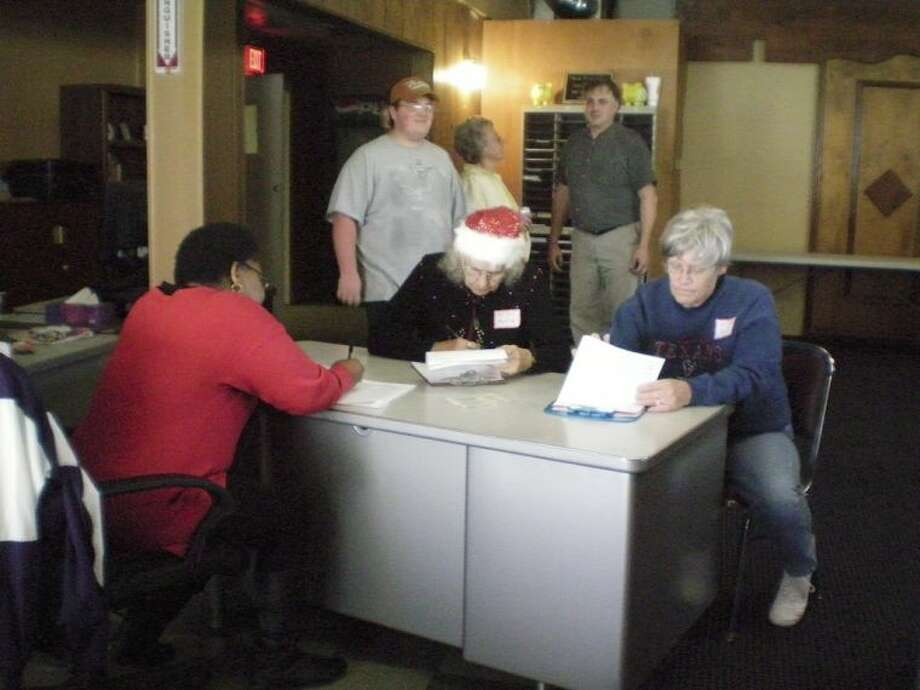 Shown here are Dayton Community Food Pantry volunteers Edna Joubert, Myrtle Hergemueller, and Karen Hare looking over lists of people to get food with Matthew Tilton looking on and Joan Jones, executive director, talking with Harry Jones. Photo: Submitted Photo
