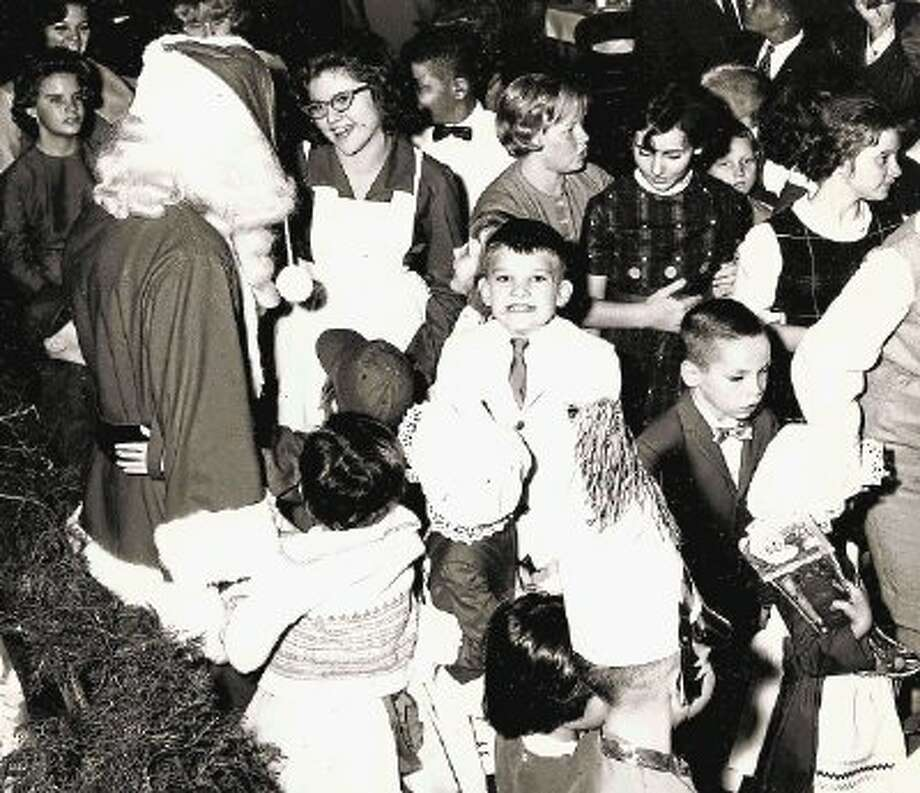 This photo, possibly dating to the 1960s, illustrates how local Rotarians helped make Christmases bright for orphaned and delinquent girls at the Harris County Training School for Girls during the first half of the 20th Century. Later accredited by the state, the school became known as the Mary Burnett School and was among several children's homes operated by the Harris County Probation Department. / @WireImgId=2655272