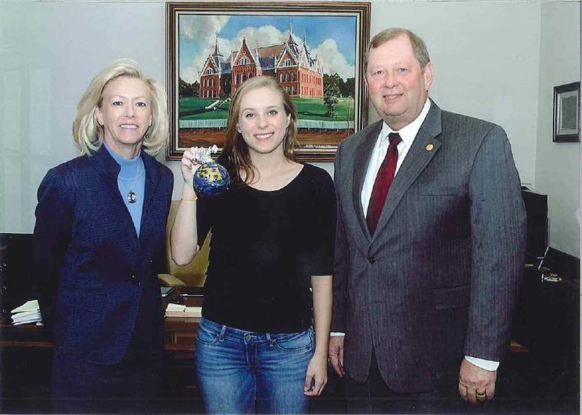 Sam Houston State University Student Ashton Leath (center) holds up the ornament she created for District 18. She is joined by State Representative John Otto.