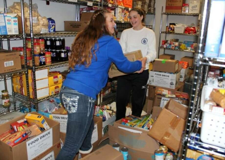 Society members help stock the center's pantry. Photo: Courtesy FBISD
