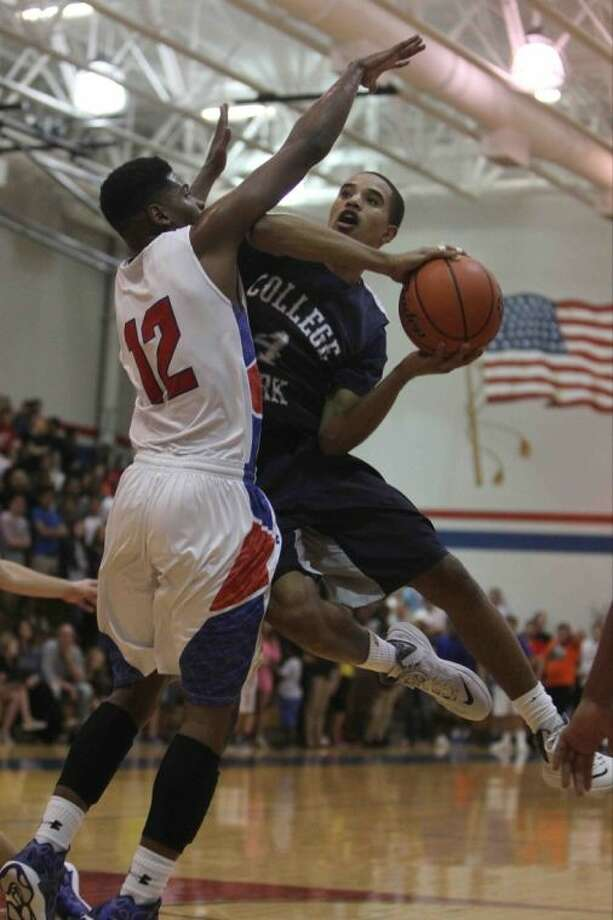 College Park guard Clinton Noel draws contact from Oak Ridge's Josh Caldwell while going up for a shot during a high school boys basketball game against Oak Ridge Friday. College Park won 77-65. To view or purchase this photo and others like it, visit HCNpics.com.