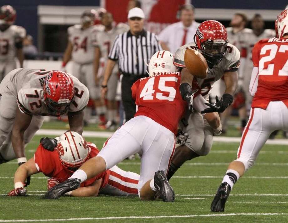 Katy's Jake Blomstrom causes a fumble against Cedar Hill's Peter Lewis during the 5A Division II Football State Championship game Dec. 21 at AT&T Stadium in Arlington. Katy led into the fourth quarter but fell 34-24. To view or purchase this photo and others like it, go to HCNPics.com. Photo: Alan Warren