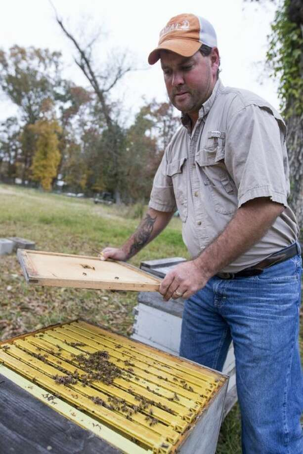 "Dayton beekeeper John Tucker shows off his beehives at a friend's home north of Dayton. Tucker was recently featured on the National Geographic Channel's ""Doomsday Preppers"" for his unique survival plan including a custom made ""bug out"" vehicle for his beehives. Photo: ANDREW BUCKLEY"