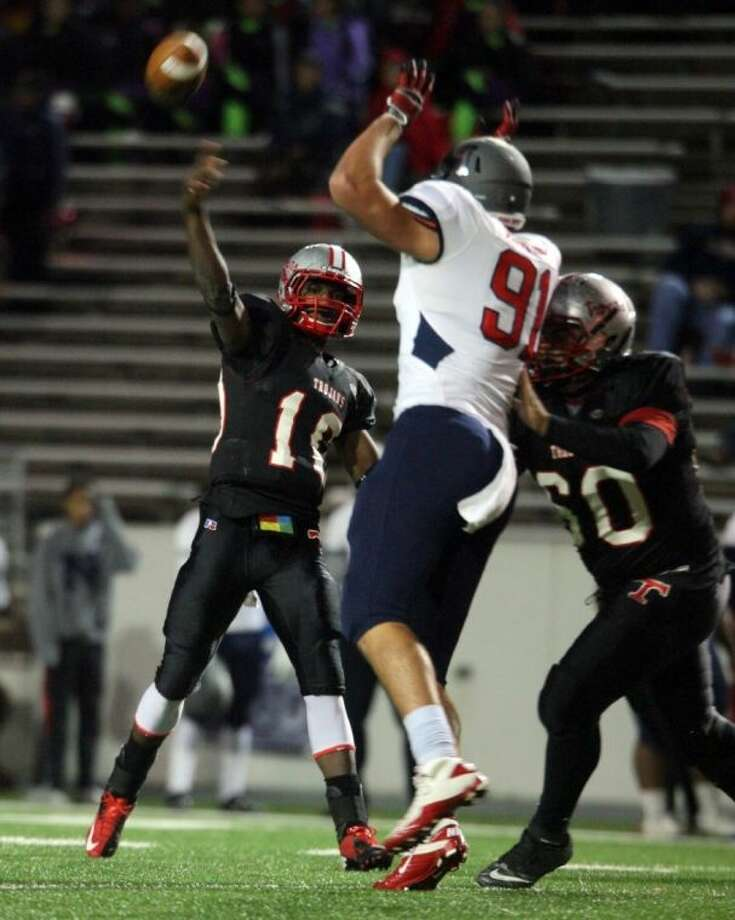 South Houston quarterback James Davis attempts to pass over the big burly arms of a Manvel lineman in the district finale last month. The 22-5A coaches honored Davis for a second straight year by naming him to the All-District Team. Photo: Robert Avery