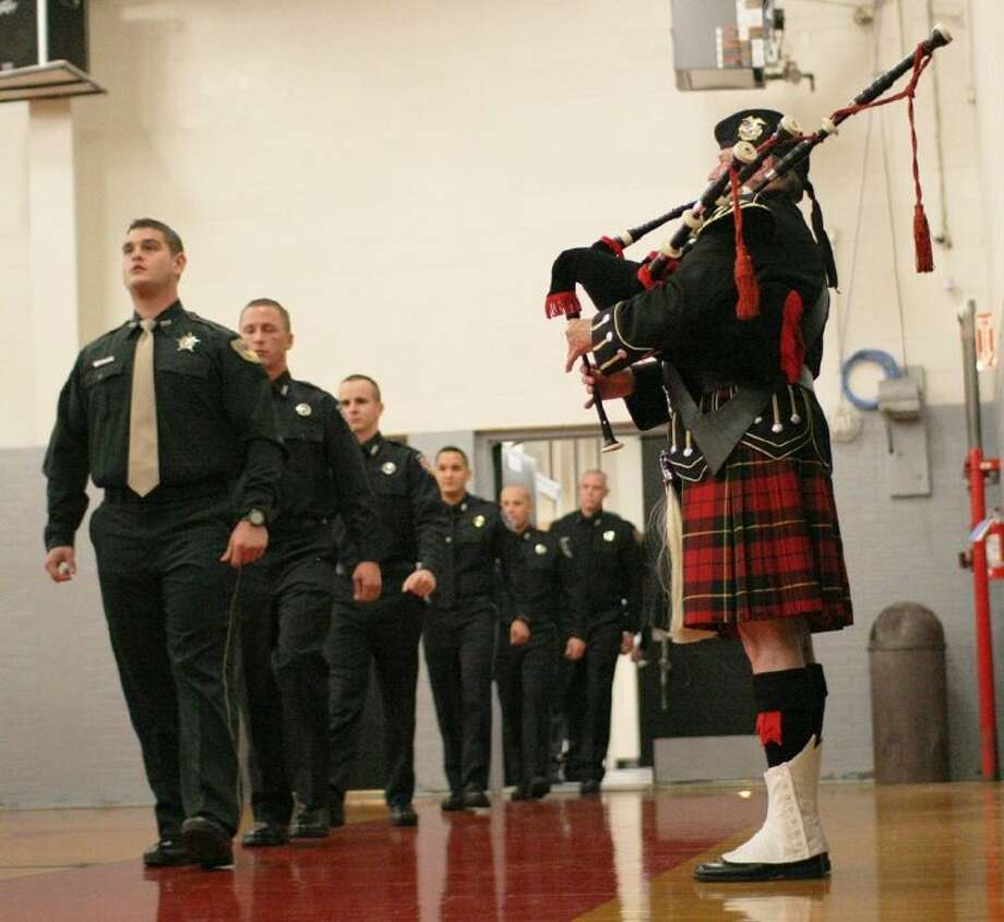 ACC Law Enforcement Academy cadets step into the Gym with the bagpipe procession at the beginning of their graduation ceremony on December 12.
