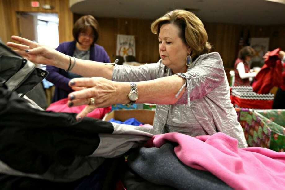 Cindy Doyle, Klein ISD Director of Community Relations and Education Foundation, sorts donated coats by size as part of the Claus Project, a project that helps provide coats to various under privileged Klein ISD schools, on Dec. 18, 2013, at the Klein ISD Administration Building.