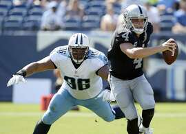 Oakland Raiders quarterback Derek Carr (4) scrambles away from Tennessee Titans nose tackle Al Woods (96) in the second half of an NFL football game Sunday, Sept. 25, 2016, in Nashville, Tenn. (AP Photo/Mark Zaleski)