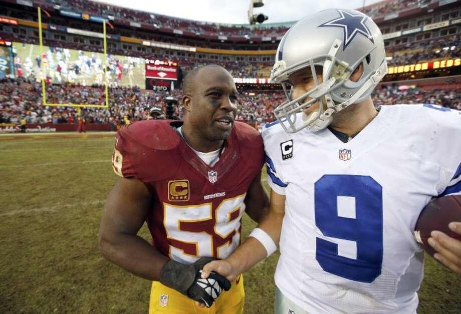 Redskins linebacker London Fletcher greets Cowboys quarterback Tony Romo, right, after the Cowboys' dramatic 24-23 victory on Sunday.